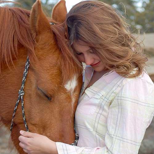 Horseback rider hugging her horse.